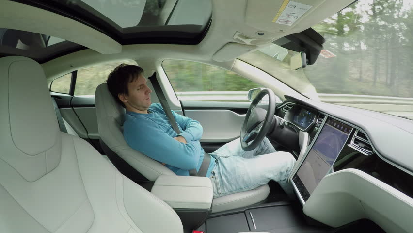 Male driver sleeping behind the self-driving steering wheel of an autonomous autopilot driverless car. Man fell deeply asleep while driving along the countryside road in luxury all-electric vehicle | Shutterstock HD Video #24508487