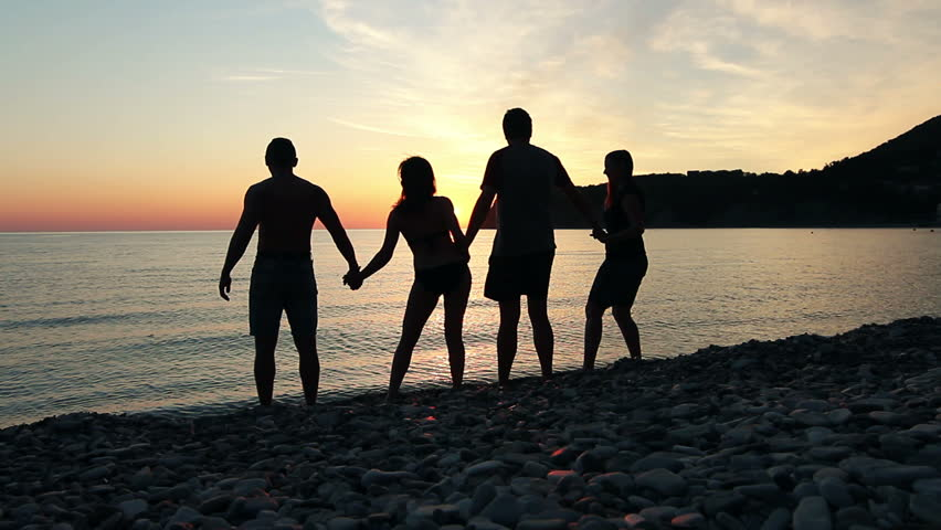 Group of people dancing on the beach at sunset, group of happy young people
