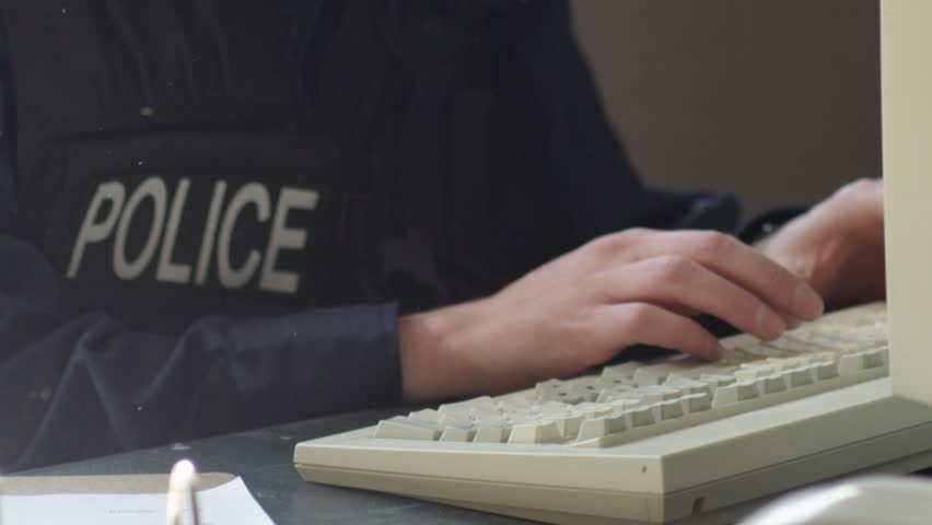 Police on keyboard filing reports close up