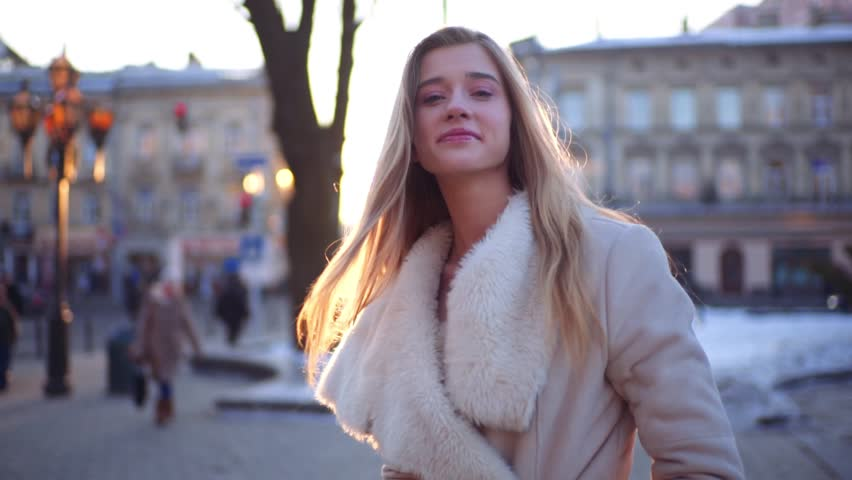 Young beautiful girl walks down the busy street with her hair loose, turns around laughing to the camera and then continues her walk. | Shutterstock HD Video #24688676