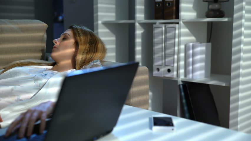 Tired businesswoman sleeping on the couch in the office with laptop and phone at night. Dolly shot   Shutterstock HD Video #24693977