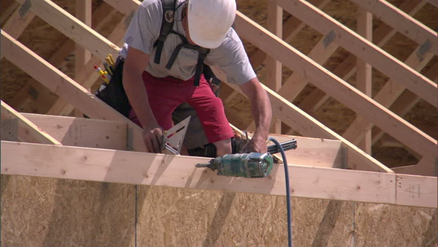 Construction worker nails together rafters of a new home. - HD stock video clip