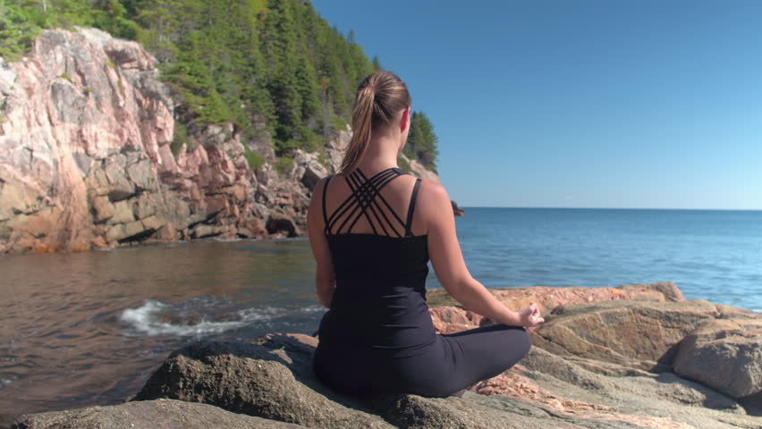 CLOSE UP: Attractive young woman meditating sitting on red volcanic rocky shore and enjoying relaxing sunny spring day. Girl relaxing doing meditation by the seashore in lush overgrown wilderness | Shutterstock HD Video #24947597