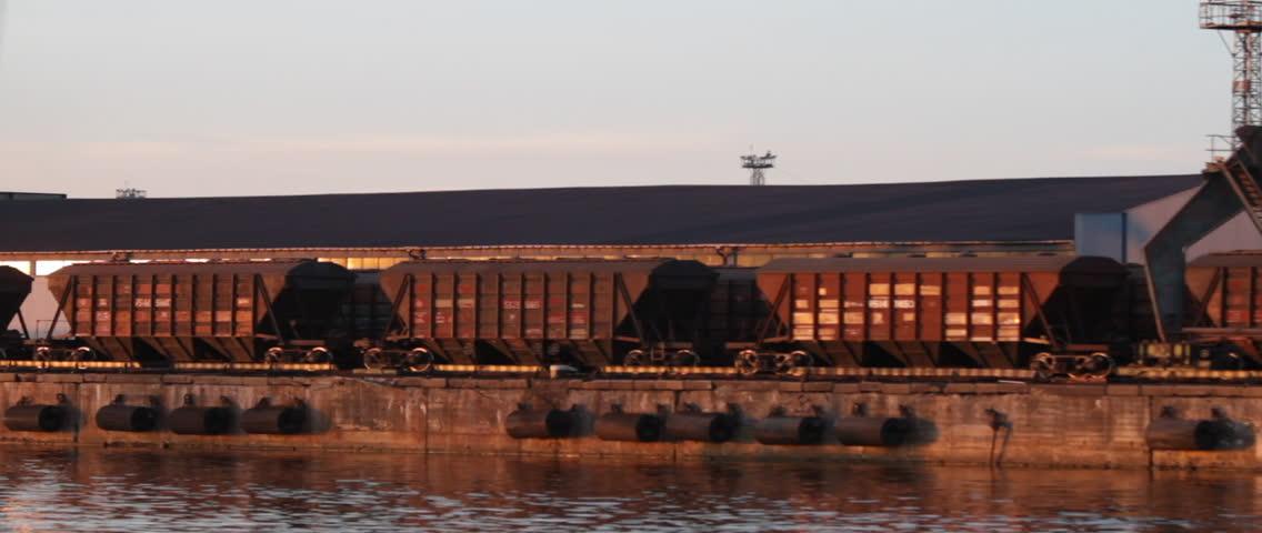 Sailboat moving at the Riga Freeport along the Daugava river, in Riga, Latvia. Freight train in the background.