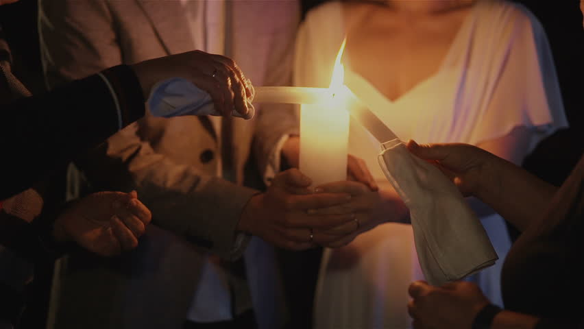 Bride and groom lighting up a candle as a symbol of love | Shutterstock HD Video #25058234