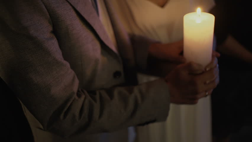 Bride and groom lighting up a candle as a symbol of love | Shutterstock HD Video #25058243