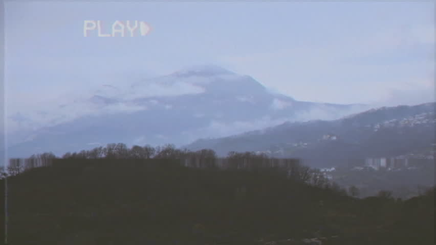 Fake VHS tape: a mountain view on a slow morning. Snow-capped peaks and green bushes.