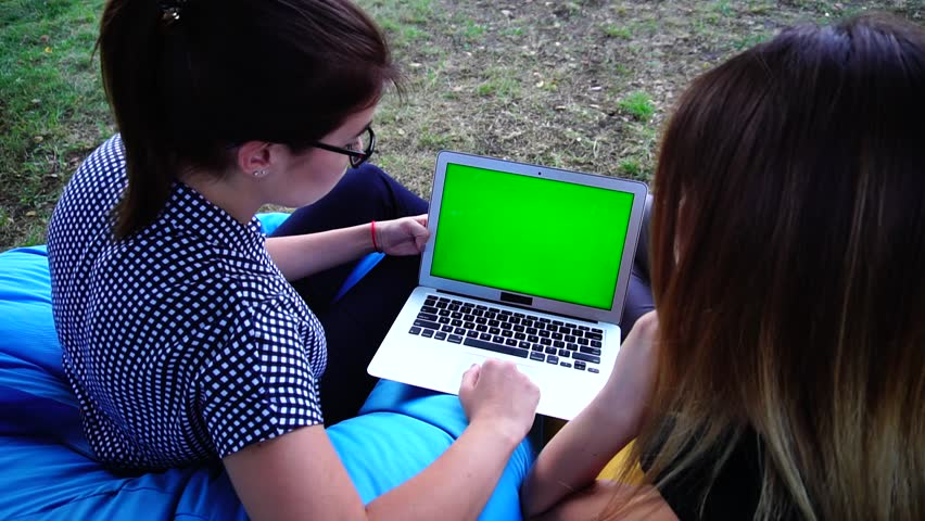 Two Educated, Young and Good-Looking Women Discuss Business and Technology News, Look at Green Laptop Screen, Sitting in Soft and Comfortable Colored Armchairs Amidst Green and Large Outdoor Park in | Shutterstock HD Video #25116311