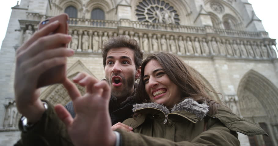 Tourist couple taking selfie photograph in front of Notre Dame Paris smartphone in city sharing lifestyle photo enjoying  holiday European   vacation travel adventure   Shutterstock HD Video #25161653