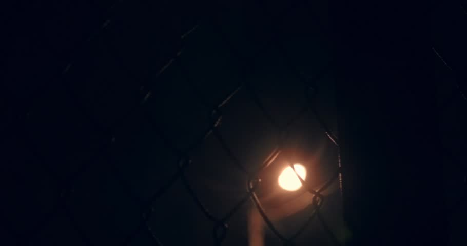 Scene: street sports at night. Mesh fencing the stadium under the light. The light of the lantern passes through the fence grid. The camera crosses the object. | Shutterstock HD Video #25162436