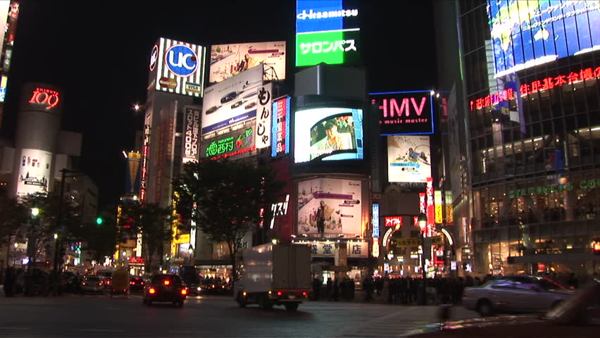 Tokyo, Japan - CIRCA November, 2006: Traffic drives past the camera in a busy intersection with many large billboards during the evening rush hour - HD stock video clip