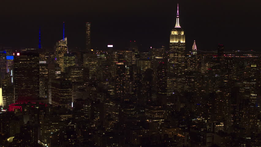 AERIAL HELI SHOT, COPYRIGHT FREE: Iconic skyline of Empire State Building, Chrysler Building and Times Square skyscraper with Upper Manhattan. New York City at night with blurred and deleted logotypes