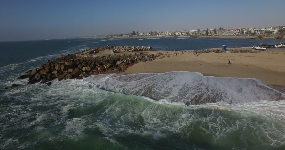Drone video of view of Namibian Atlantic coastline, Swakopmund town buildings, beach, old pier, surf break point and landscape of ocean background of Swakopmund holiday resort at Namibia's west coast | Shutterstock HD Video #25185854