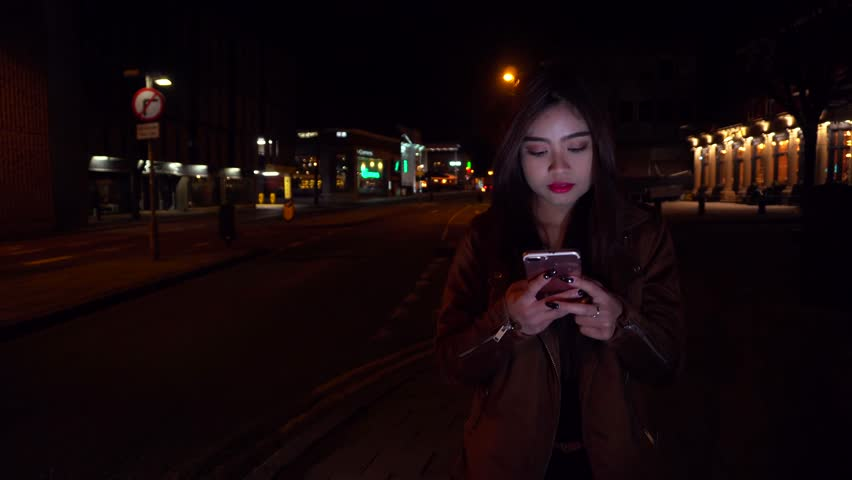 Attractive Asian young lady texting sms / swiping app on a mobile smart phone at night / evening whilst walking. Natural lighting pink neon on girl. Professional urban beautiful female in her 20s | Shutterstock HD Video #25186106