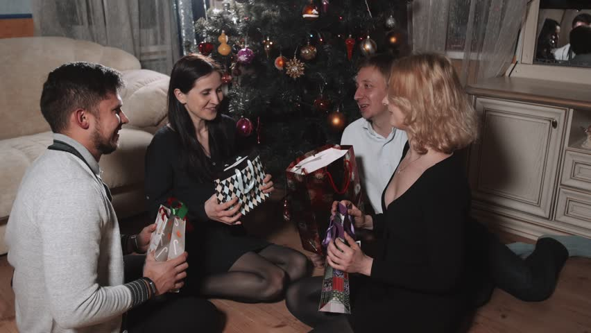 Group of Young People Give Presents To Each Other Under The Tree In The Christmas Interior, New Year Celebration | Shutterstock HD Video #25191056
