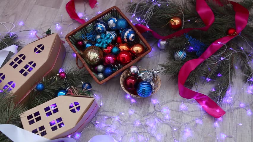 Many Christmas balls and a flicker of a garland on a wooden background. Cardboard houses on a New Year's background | Shutterstock HD Video #25209452