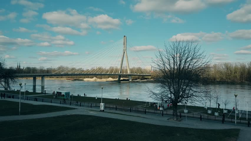 Aerial rising shot of Vistula river embankment and Holy Cross cable bridge in Warsaw, Poland. 4K video | Shutterstock HD Video #25223267