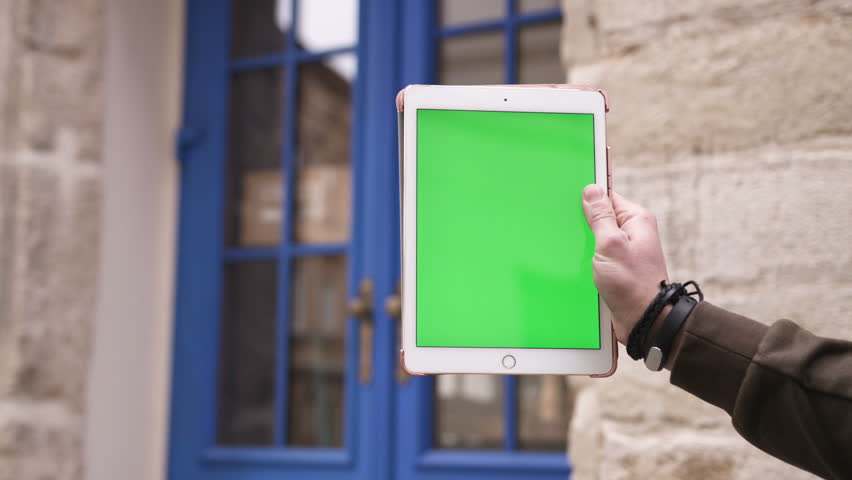 Closeup hand of man holding tablet computer with vertical green screen in the background blue door | Shutterstock HD Video #25230377
