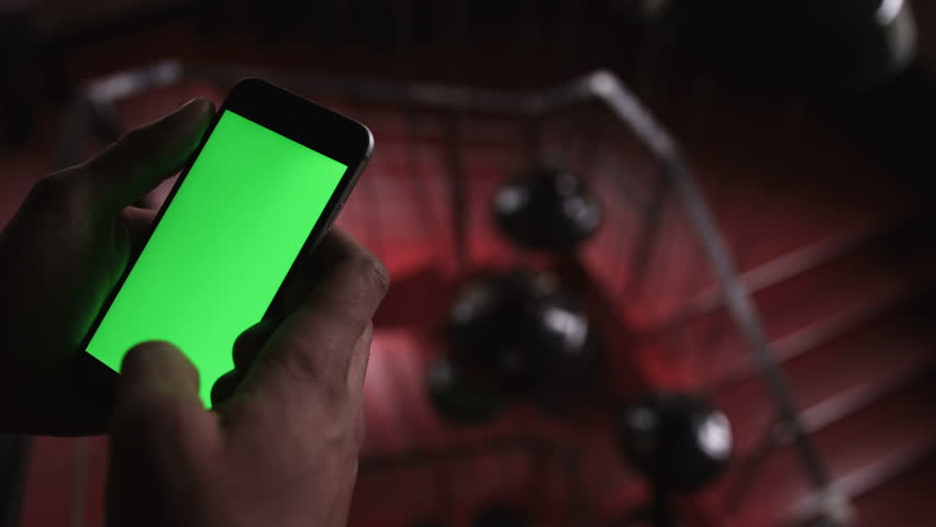 Close-up of a man holding and touching the phone with green screen in the background red stairs | Shutterstock HD Video #25230395