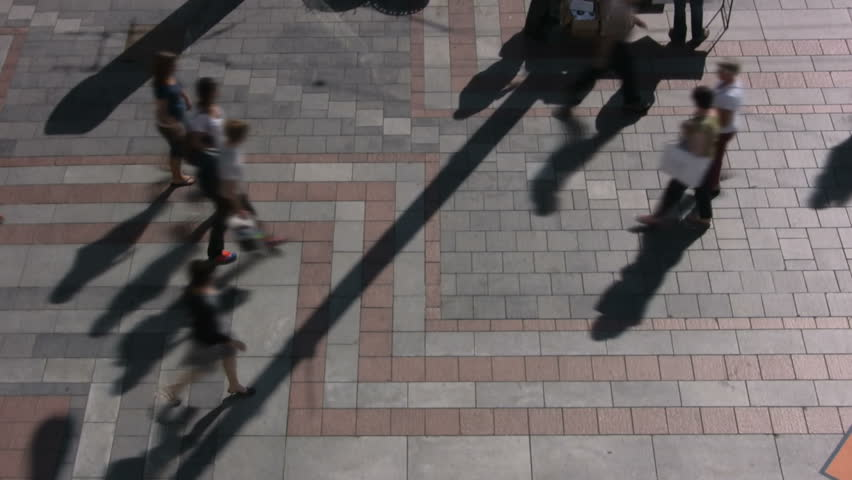 Time lapse aerial shot of people walking on city plaza with shadows  - HD stock video clip