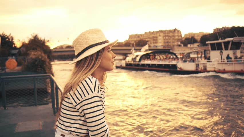 Woman tourist in Paris. Traveller female in hat relaxing, beautiful sunset near the Seine river.    Shutterstock HD Video #25288562
