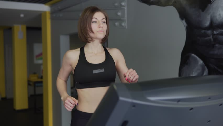 A woman in a sport suit warms the muscles on the simulator before training. The athlete is engaged in active running on the treadmill in order to prepare for the power training. | Shutterstock HD Video #25315112