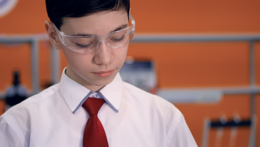 Student at school doing a science experiment using reagents, test tube and laser. | Shutterstock HD Video #25344443