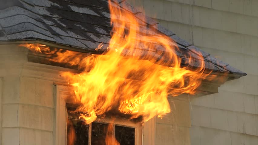 Flames pouring out of window of house on fire - closeup