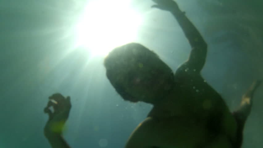 Man underwater, going back to the surface.