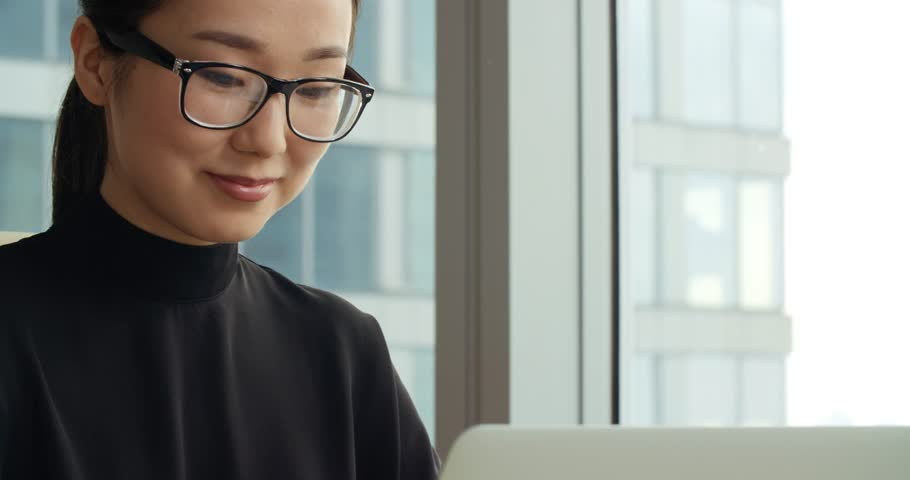 Closeup of a young successful Asian business girl in a modern office, working using laptop   Shutterstock HD Video #25500764