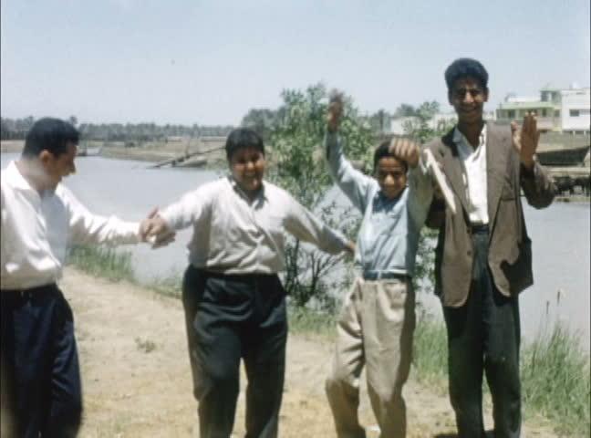IRAQ - JULY 1956: Iraqi boys dancing along the banks of the Euphrates, Iraq. Shot on 16mm film.