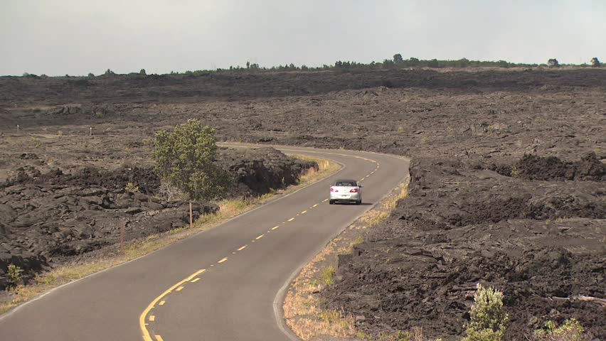 A Car Drives On A Road going Through a Lava Field - HD stock footage clip