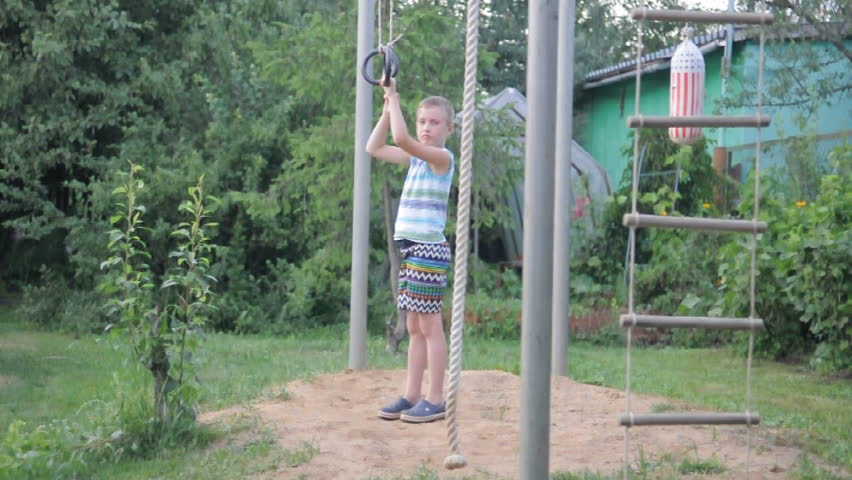 young funny boy exercising on gymnastic rings and laughing