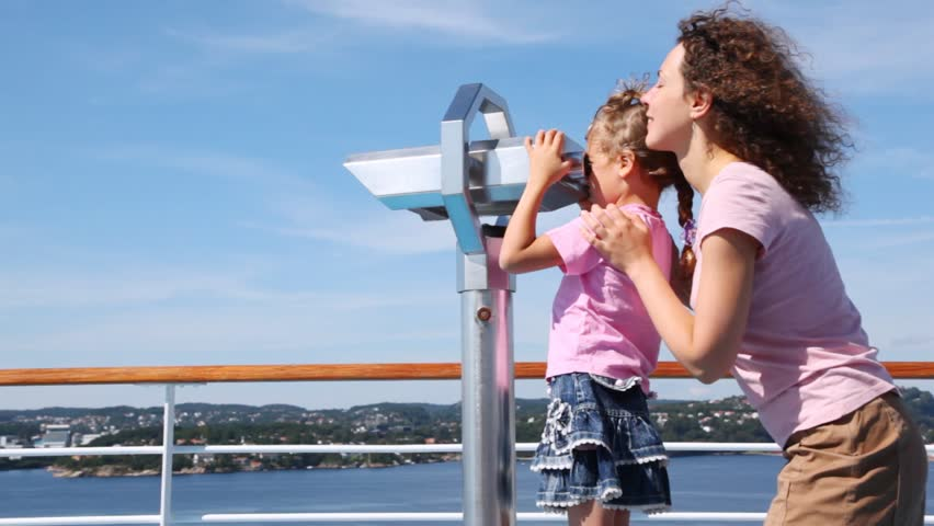 Girl looks in binocular on ship deck under direction of mother #2571338