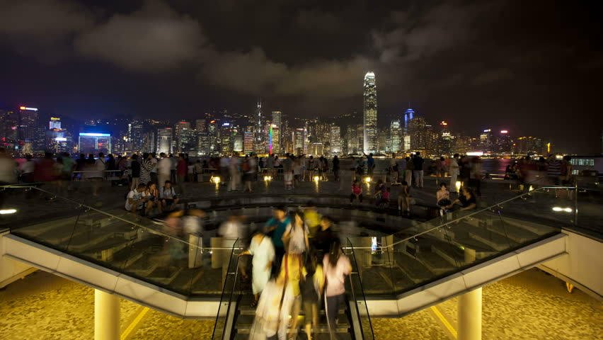 HONG KONG - CIRCA MAY 2011: People watching the world famous Sound and Light show, Hong Kong City skyline looking across Victoria harbour at night