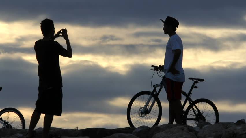 boys take pictures with cellphone on mountain after long bike ride  - HD stock video clip
