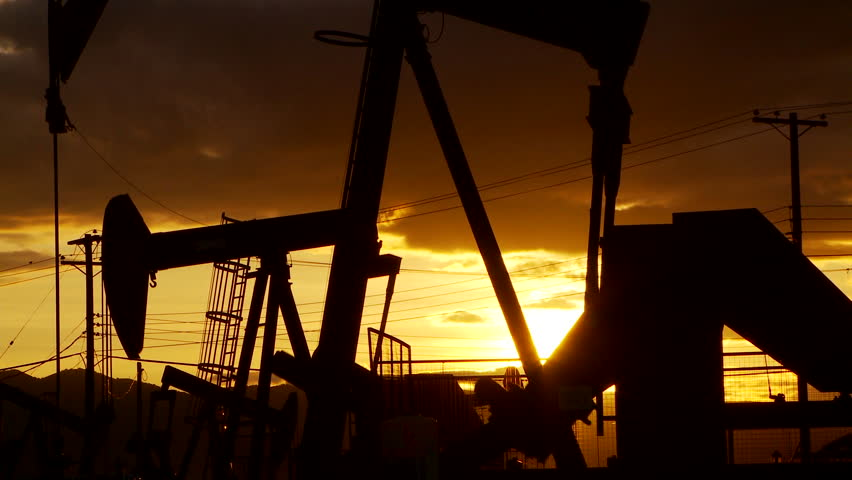 Oil well piston pumps at sunset - HD stock footage clip