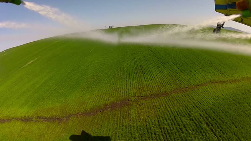 Spray leaving the nozzles of a spray plane/crop duster on a field of wheat