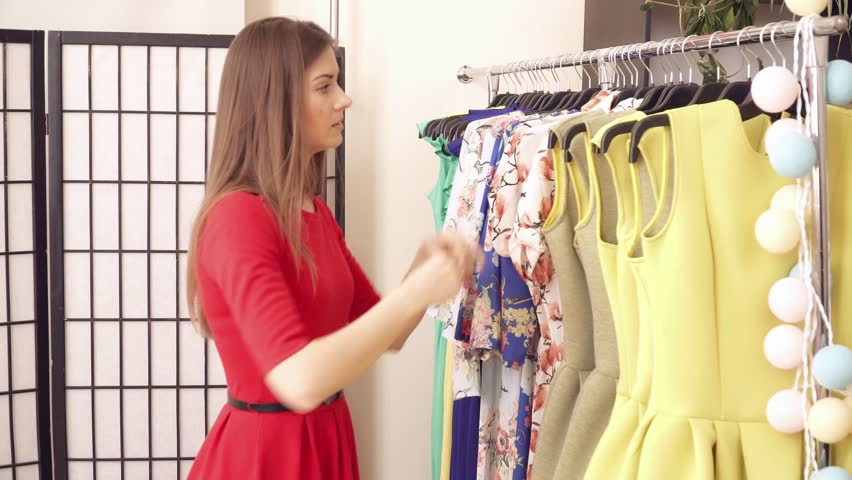 Young woman taking clothes to try on in the clothes boutique | Shutterstock HD Video #25946030