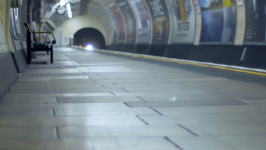 An underground train arrives at a platform and passengers get off.