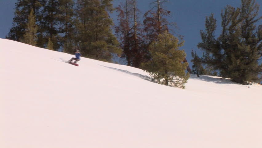 Female snowboarder carving through back-country powder - HD stock footage clip