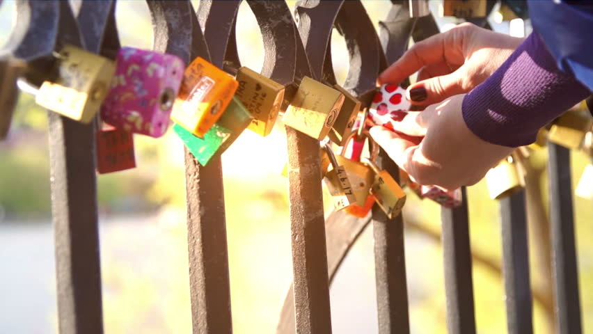 Girl (woman) hang a padlock of love on the fence of the bridge | Shutterstock HD Video #26112458