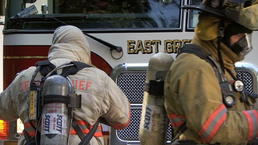 EAST GREENWICH, RHODE ISLAND - CIRCA AUGUST 2010: Fireman putting on helmut at house on fire