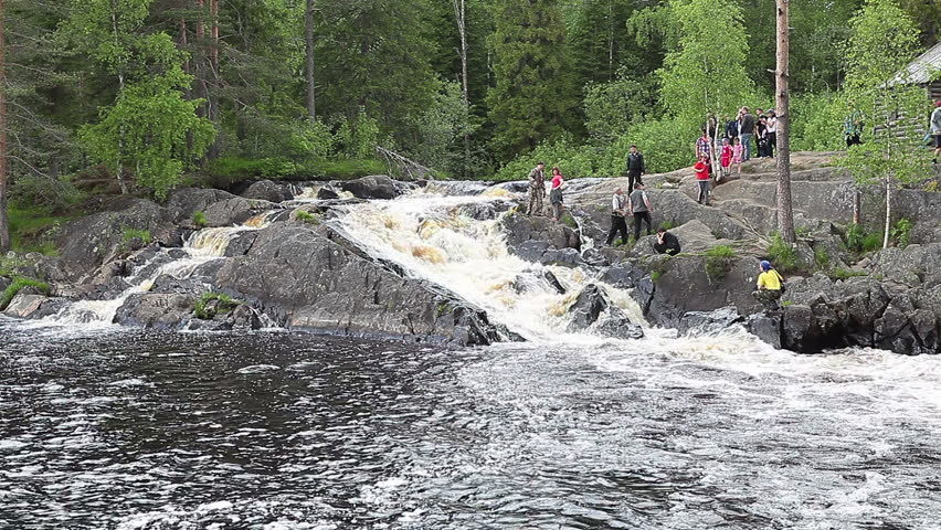 Tourists visit Ruskeala waterfalls - four falls flat in Sortavala region on the river Tohmajoki on circa June, 2012 in Ruskeala, Karelia, Russia - HD stock footage clip
