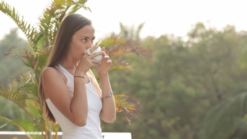 Happy woman comes out on terrace in the morning and drinking tea or coffee with palm trees garden on the background | Shutterstock HD Video #26158781