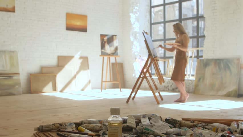 Girl artist paints on canvas on easel and holds palette in art workshop | Shutterstock HD Video #26184836