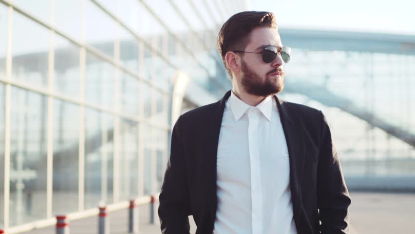 Handsome bearded man in sunglasses walking near the airport terminal, answers the phone call, nodes. Stylish elegant outfit. Being a boss, successful lifestyle. Making money, business travel. | Shutterstock HD Video #26209064