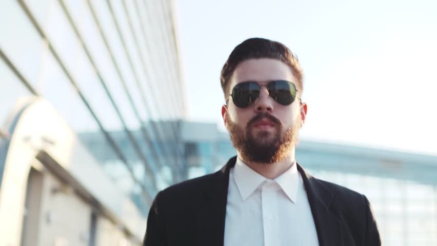 Stylish young bearded man in sunglasses exiting the airport terminal with luggage, talking on the phone. Business style, traveler, modern lifestyle. Active lifestyle. | Shutterstock HD Video #26209091
