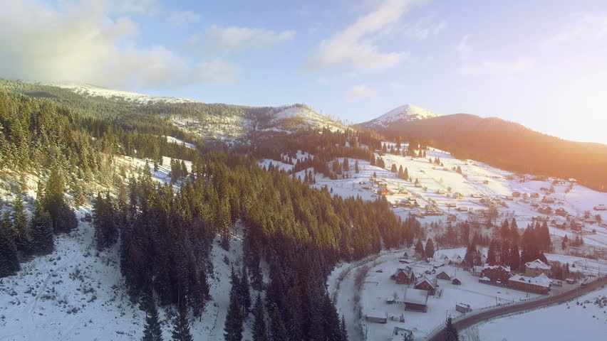 4K Aerial Drone View: Flight over Ski resort village in winter, sunset time. Houses and hotels for tourists. Pine tree forest around. Majestic nature landscape. Bukovel, Carpathian Mountains, Ukraine | Shutterstock HD Video #26219018