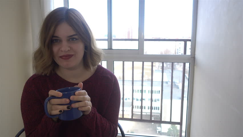 Beautiful Girl Drinking Tea or Coffee at home. Beauty Model Woman enjoying the Cup of Hot Beverage | Shutterstock HD Video #26220467